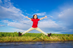 Girl jumping on wet road. Happy girl jumping on wet road after rain Stock Photography