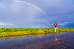 Girl jumping on wet road with rainbow. Happy girl jumping on wet road with rainbow after rain, with copy-space Royalty Free Stock Photos