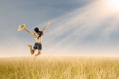Girl jumping in wheat field Stock Photos