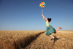 Girl jumping with wind turbine at wheat field Stock Images