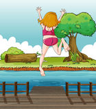 A girl jumping at the wooden bridge Royalty Free Stock Images
