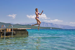 Girl jumping from a wooden pier in the sea Stock Photography