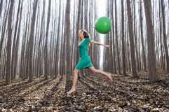 Girl jumping into the woods with a big balloon. Beautiful blonde girl, dressed in green, jumping into the woods with a balloon in Fuente Vaqueros, Granada, Spain Stock Images