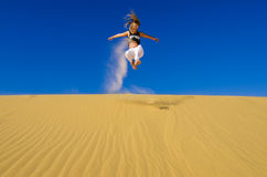 Girl jumping on the yellow sand dune Royalty Free Stock Image