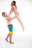 Girl jumping in young man arms with their swimming clothes Royalty Free Stock Image