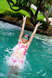 Girl jumps backward into swimming pool Stock Images