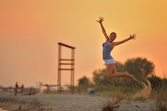 Girl jumps on the beach. A girl is jumping on the beach with hands up in beautiful sunset light, speading out pieces of sand in the air and shows up her Royalty Free Stock Photo