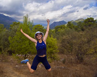 Girl jumps cheerfully on autumn forest path. Girl wearing dark blue sport outfit, blue panama and sunglasses jumps cheerfully on a green forest path Royalty Free Stock Photography