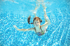 Girl jumps, dives and swims in pool underwater, happy active child has fun under water, kid sport Stock Images