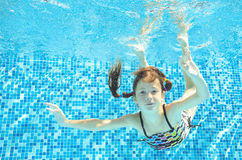 Girl jumps, dives and swims in pool underwater, happy active child has fun under water, kid sport royalty free stock image