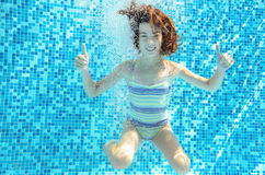 Girl jumps, dives and swims in pool underwater, happy active child has fun under water, kid sport o Stock Photo