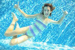 Girl jumps, dives and swims in pool underwater, happy active child has fun under water, kid sport o Royalty Free Stock Images