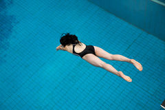 Girl jumps from a diving board at swimming pool Stock Images