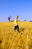 Girl jumps in golden field Stock Image