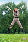 The girl jumps on a grass and trees as a backgroun Royalty Free Stock Photos
