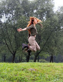 Girl jumps on a grass and trees as a background Stock Images