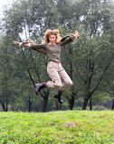 Girl jumps on a grass and trees as a background Stock Image