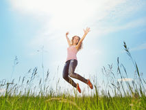 Spring Girl. The girl jumps on a green grass Royalty Free Stock Image