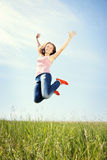 Spring Girl. The girl jumps on a green grass royalty free stock photo