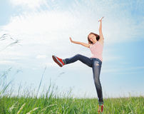 Spring Girl. The girl jumps on a green grass Stock Image