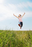 Spring Girl. The girl jumps on a green grass Stock Photography