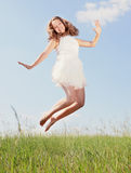 Spring Girl. The girl jumps on a green grass royalty free stock images