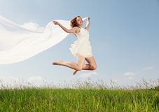 Spring Girl. The girl jumps on a green grass stock images