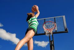 Girl jumps high. Teen plays basketball and puts ball right in basket Royalty Free Stock Photo