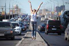 Girl jumps on highway middle Stock Photo