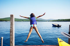 Girl jumps in the lake. Little girl leaps off the end of the dock into a lake stock photo