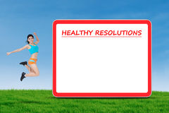 Girl jumps near a board of healthy resolutions Stock Images