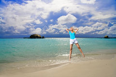 The girl jumps on an ocean coast Stock Photography