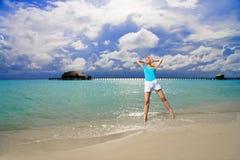 The girl jumps on an ocean coast Stock Photography