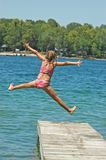 Girl Jumps Off Dock. Young Girl Jumps Off Dock into Lake Extending Arms and Legs Royalty Free Stock Photography