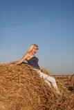 The girl jumps off from a haystack in th Stock Image