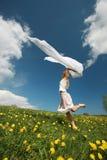 Girl jumps over dandelion field Stock Photo