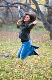 Girl  jumps in the park in autumn Stock Images
