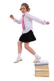 Girl jumps from a pile of books Royalty Free Stock Photography