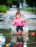 Girl jumps into a puddle. Happy little girl, wearing a pink jacket,  jumps into a puddle Stock Images
