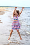 Girl jumps in sea Stock Images