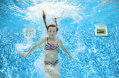 Girl jumps and swims in pool underwater, child has fun in water. Girl jumps and swims in pool underwater, happy active child has fun in water, kid sport on Royalty Free Stock Photography