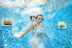 Girl jumps and swims in pool underwater, child has fun in water. Girl jumps and swims in pool underwater, happy active child has fun in water, kid sport on Royalty Free Stock Photos