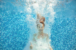 Girl jumps and swims in pool underwater, child has fun in water Stock Photo