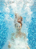 Girl jumps and swims in pool underwater, child has fun in water Stock Photos