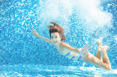 Girl jumps and swims in pool underwater, child has fun in water Royalty Free Stock Image