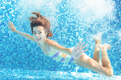 Girl jumps and swims in pool underwater, child has fun in water Stock Photography