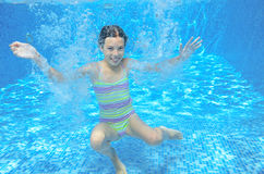 Girl jumps and swims in pool underwater, happy active child has fun under water Stock Photos