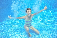 Girl jumps and swims in pool underwater, happy active child has fun under water Stock Image