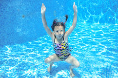 Girl jumps and swims in pool underwater, happy active child has fun under water Royalty Free Stock Photo