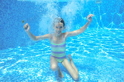 Girl jumps and swims in pool underwater Stock Photo